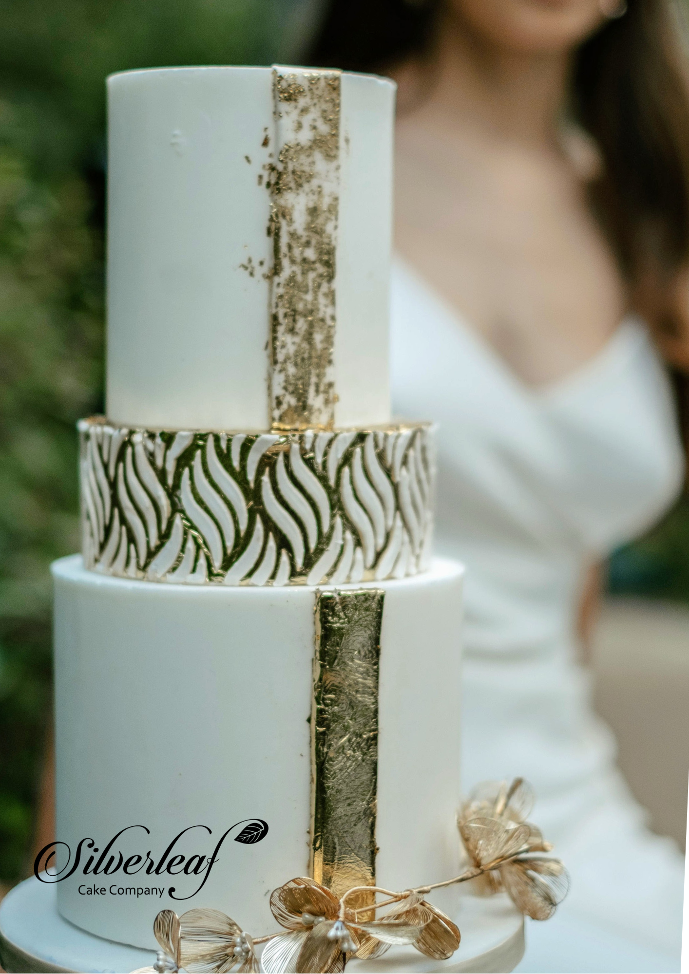 Sharp three-tier white and gold wedding cake. Top and bottom tier are white with a brioad raised gold line detail and middle tier is golf leaf with modern stencil detailing in white. Very simple, elegant and quietly outspoken