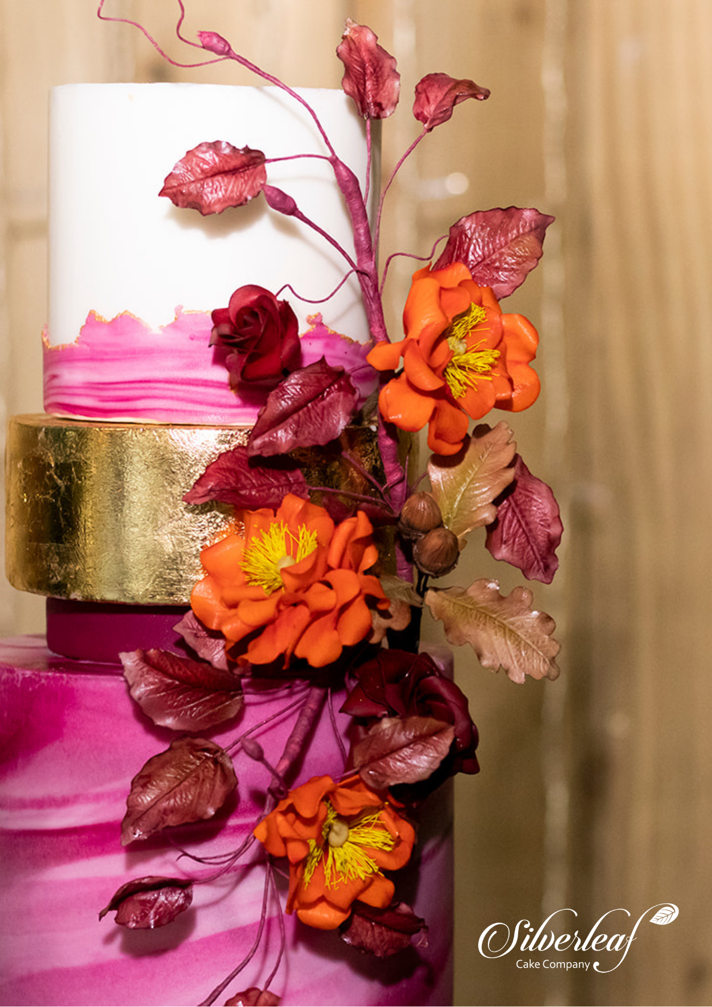 Three tier Dark and Pale Pink Marble Wedding Cake. Middle tier is fully gold leaf. Top tier is white with pink marble detailing. Finished with intricate orange sugar flowers, contrasting pink leaves and acorns